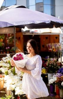 Bela jovem comprando flores no mercado de flores