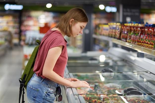 Bela jovem concentrada com penteado cortado, vestida casualmente, escolhe os produtos necessários na geladeira