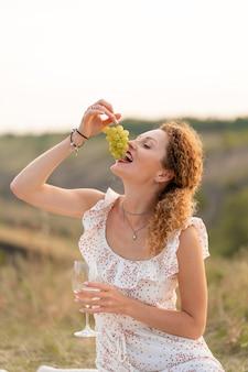 Bela jovem concurso ruiva em um vestido de verão branco, come uvas e bebe vinho na natureza.