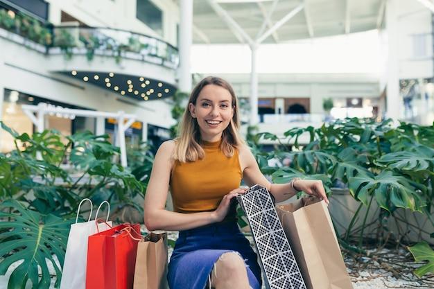 Bela jovem considera suas compras feitas no supermercado durante os descontos
