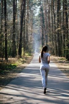Bela jovem correndo no parque verde em dia de verão ensolarado