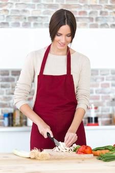 Bela jovem cortando legumes frescos na cozinha.