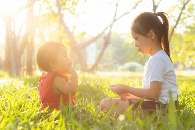 Bela jovem criança asiática sentado jogando no verão