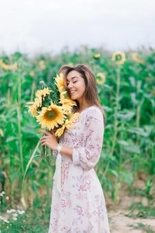 Bela jovem curtindo a natureza no campo de girassóis ao pôr do sol