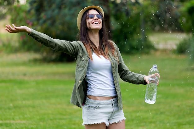 Bela jovem curtindo verão com água.