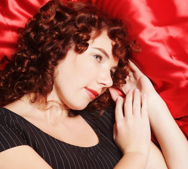 Bela jovem curvilínea em lingerie deitada na cama.