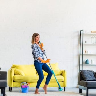 Bela jovem dançando com esfregão na sala de estar