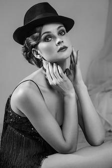 Bela jovem dançarina caucasiana de vestido preto e maquiagem moda e chapéu posando em pé de joelhos e olhando para a distância. tiro do estúdio. foto em preto e branco.
