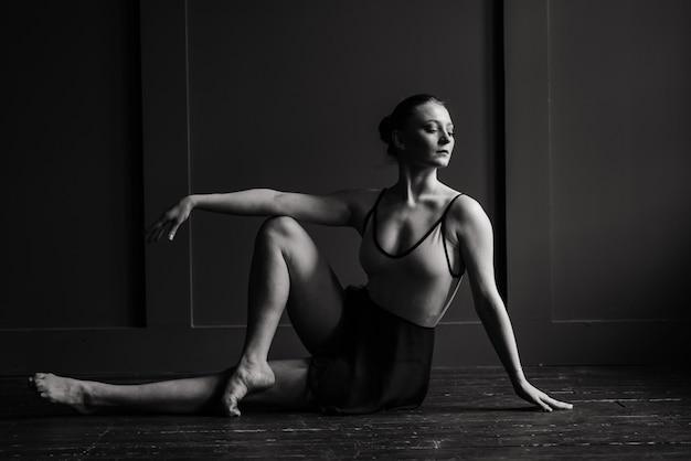 Bela jovem dançarina de balé clássico em sapatilhas de ponta, vestindo um collant preto e saia em uma parede de tijolos