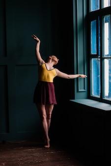 Bela jovem dançarina de balé clássico em sapatilhas de ponta, vestindo uma malha preta e saia em um fundo de estúdio