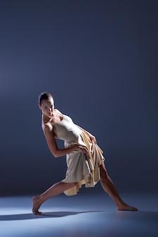 Bela jovem dançarina em um vestido bege dançando no fundo cinza do estúdio