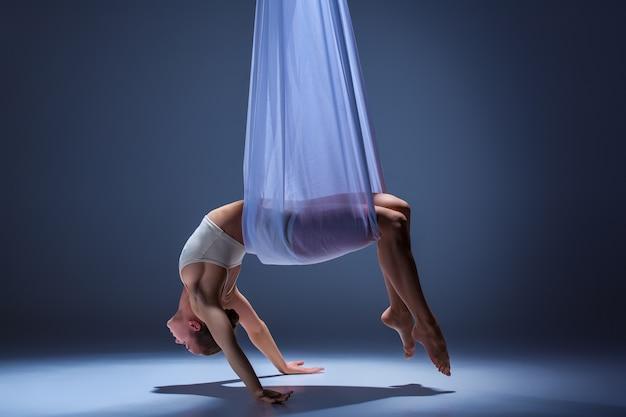 Bela jovem dançarina em um vestido bege posando com rede de tecido no fundo cinza do estúdio