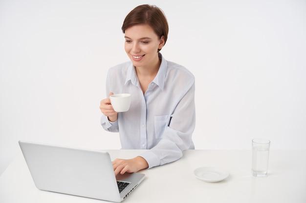 Bela jovem de aparência agradável com cabelo castanho e corte de cabelo curto na moda, sorrindo positivamente enquanto verificava sua caixa de correio, posando em branco com uma xícara de chá