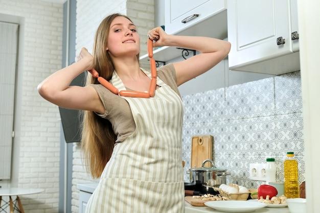 Bela jovem de avental cozinhando em casa, na cozinha, sorrindo, mulher segurando salsichas nas mãos, nutrição saudável caseira