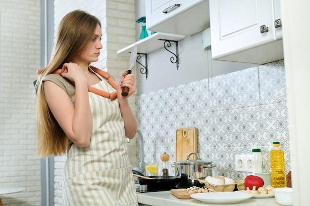 Bela jovem de avental cozinhando em casa na cozinha