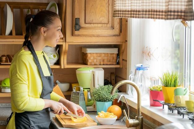 Bela jovem de avental preto cozinhando na cozinha de uma aconchegante casa de campo de madeira cortando pimentões