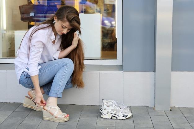 Bela jovem de cabelo comprido endireita a fivela dos sapatos novos na rua