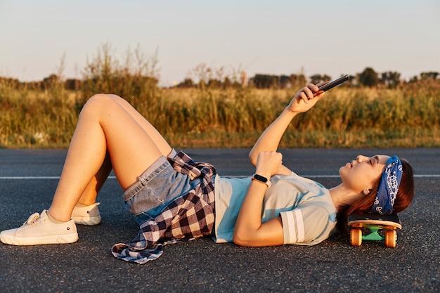 Bela jovem de cabelos escuros deitou-se na estrada de asfalto ao ar livre com a mão no skate, usando um telefone celular para tirar selfie ou cheking nas redes sociais.