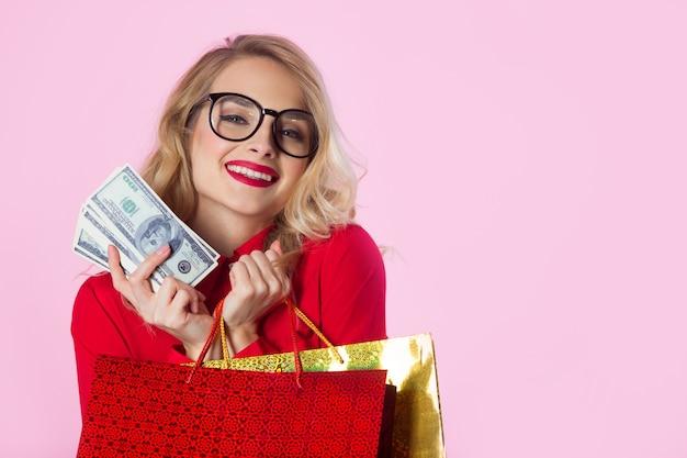 Bela jovem de camisa vermelha com dólares e pacotes nas mãos em uma parede rosa