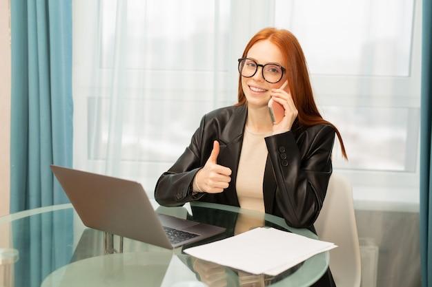 Bela jovem de óculos com cabelo vermelho na mesa com um laptop no escritório