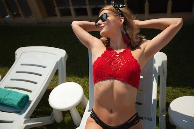 Bela jovem de óculos de sol tomando banho de sol em uma espreguiçadeira branca perto da piscina no verão
