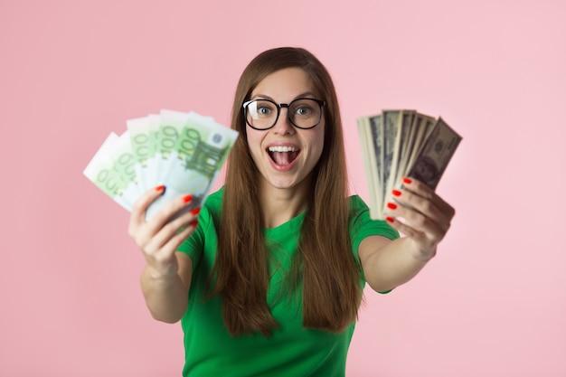 Bela jovem de óculos detém euros e dólares em um fundo rosa
