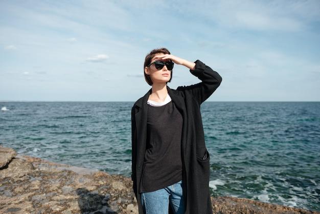 Bela jovem de óculos escuros e casaco preto em pé e olhando para longe na beira-mar Foto Premium