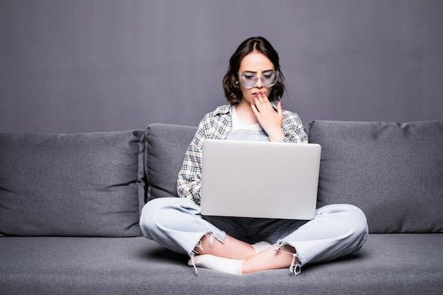 Bela jovem de óculos usando um laptop em casa, sentada no sofá
