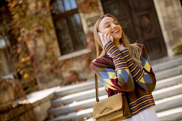 Bela jovem de pé com o celular na rua no dia de outono