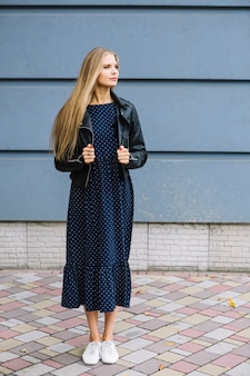 Bela jovem de pé na frente de parede segurando usava jaqueta