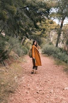 Bela jovem de pé na trilha de montanha, segurando o livro na mão