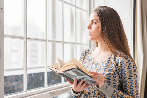 Bela jovem de pé perto da janela, segurando o livro na mão, olhando para longe