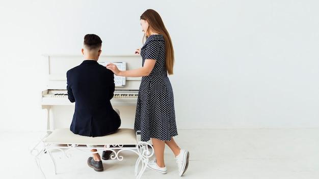 Bela jovem de pé perto do homem tocando piano
