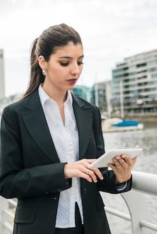 Bela jovem de pé perto do porto tocando no celular