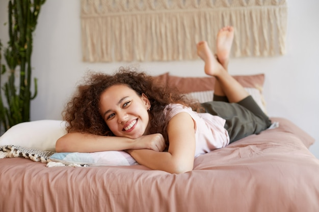 Bela jovem de pele escura encaracolada deitada na cama, aproveite o dia ensolarado em casa, sorrindo amplamente e sonhando com um vestido novo.