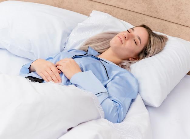 Bela jovem de pijama azul deitada na cama, descansando em travesseiros macios, dormindo pacificamente em casa no interior do quarto, com luz de fundo
