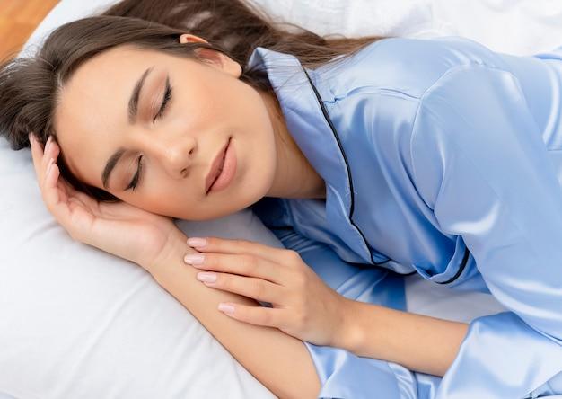 Bela jovem de pijama azul deitada na cama