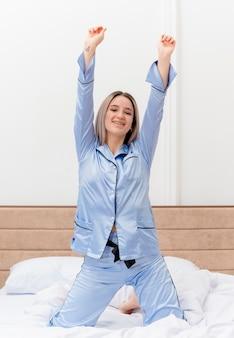 Bela jovem de pijama azul sentada na cama acordando se espreguiçando feliz e sorrindo positivamente no interior do quarto