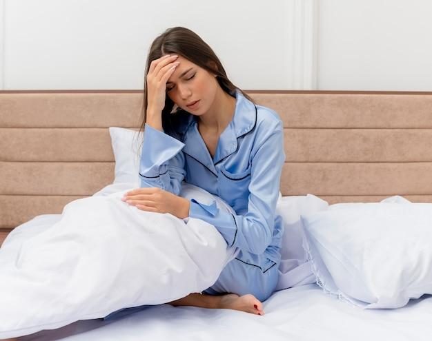 Bela jovem de pijama azul sentada na cama com uma almofada parecendo doente, tocando a cabeça com dor de cabeça no interior do quarto