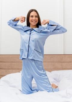Bela jovem de pijama azul, sentada na cama, descansando feliz e sorrindo positivamente, aproveitando o fim de semana no interior do quarto