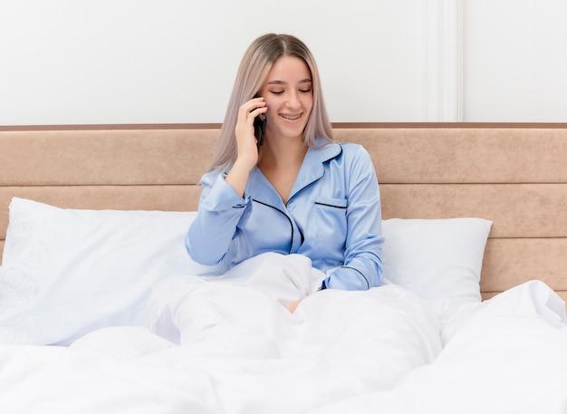 Bela jovem de pijama azul sentada na cama falando no celular e sorrindo no interior do quarto