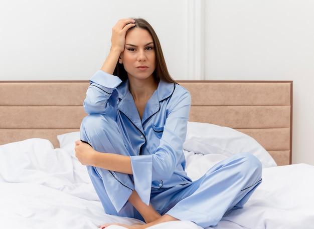 Bela jovem de pijama azul sentada na cama no interior do quarto