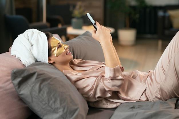 Bela jovem de pijama de seda, toalha na cabeça e máscara cosmética dourada no rosto relaxando na cama e fazendo selfie