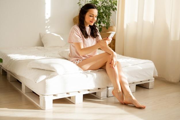 Bela jovem de pijama sentada em casa na cama com um telefone celular