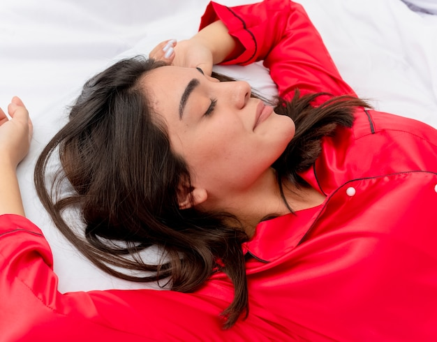 Bela jovem de pijama vermelho relaxando na cama