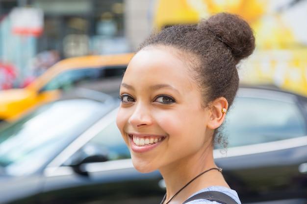 Bela jovem de raça mista na cidade, sorrindo retrato