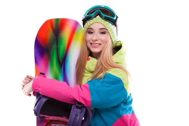 Bela jovem de roupa de esqui e óculos de esqui segurar snowboard