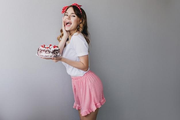 Bela jovem de saia rosa, comemorando o aniversário. garota de cabelos escuros entusiasmada dançando com um bolo doce.