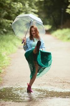 Bela jovem de saia verde se diverte andando em gumboots em piscinas após a chuva