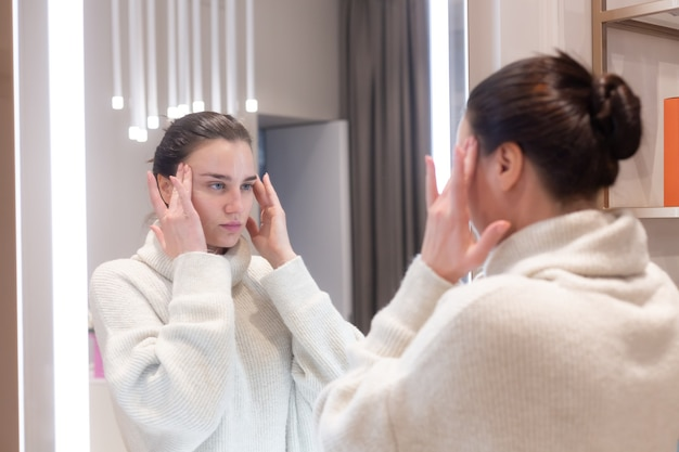 Bela jovem de suéter em um salão de beleza se olha no espelho, toca o rosto, pensa nos próximos procedimentos, considera-se